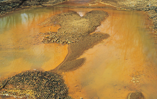 Iron hydroxide precipitate stains a stream receiving acid drainage from a mine